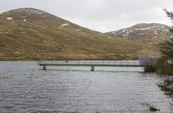 The small jetty and inspection platform at the Fofanny Water Treatment Works in the Western Mourne Mountians. With snow capped peaks on a dull midwinter stock photo