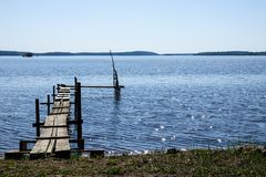 A small jetty / pier in a lake. Warm sunny day with the sun standing high royalty free stock images