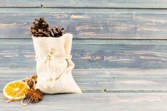 Small jute bag with pine cones, anise and  dry orange slice Stock Images