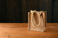 Small jute bag on wooden table Stock Photos