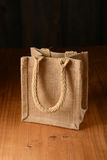 Small jute bag on wooden table Stock Images