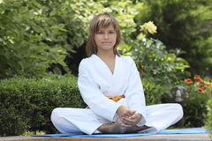Small karate. Boy karate sitting outside in the lotus position Royalty Free Stock Images