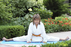 Small karate. Boy karate sitting in the splits outside Stock Images