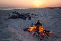 Small kettle stands on a burning bonfire. On the seaside during stunning sunset. Preparation for dinner in travelling. Amazing adventure in the wild Stock Image