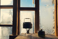 Small kettle stands on a gas burner against a window in a frost. Awesome morning in an old mountain shelter during a winter adventure Royalty Free Stock Photography