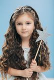Small kid angel has long crisp hair, blue eyes, holds magic wand in form of star, poses over blue background, has appealing royalty free stock photos