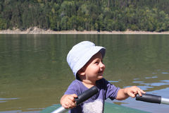 Small kid boy like fishing. A small boy rowing a boat in the middle of the river. child enjoys boating and canoeing. small kid boy like fishing stock photo