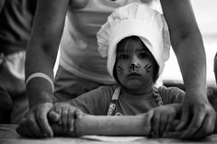 Small kid cooking homemade cake, using rolling pin with grandma on kitchen, black and white photo. Small cute kid in a kitchen with a face art cat cooking royalty free stock image