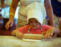 Small kid cooking homemade cake, using rolling pin with grandma on kitchen. Small cute kid in a kitchen with a face art cat cooking homemade bread royalty free stock photography