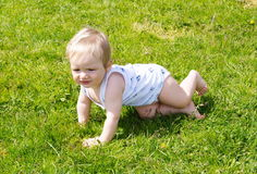 The small kid creeps on a grass. The child in a vest and swimming trunks creeps in the summer on a green lawn Stock Image