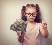 Small kid girl holding dollars and have an plan how earning much. Money in crisis. Serious child showing finger. Vintage closeup portrait Royalty Free Stock Photos