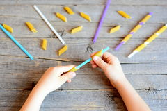 Small kid holds straw and dried tube pasta in his hands. Kid stringing pasta onto straw Stock Photos