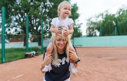 Small kid, a little girl sits on the shoulders of mom smiling, laughing, playing, having fun at tennis court. Small kid, a little girl sits on the shoulders of Stock Photography