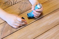 Small kid opens asthma inhaler. Inhalation treatment of respiratory diseases. Allergy and bronchial asthma medication Royalty Free Stock Image