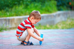 Small kid painting the ground with chalk Royalty Free Stock Images
