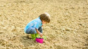 Small kid planting a flower. earth day. new life. summer farm. happy child gardener. plant nursery. Spring. ecology life. Eco farm. human and nature. organic stock photos
