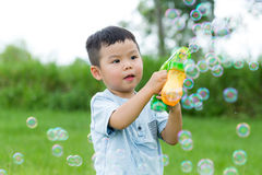 Small kid play with bubble blower. Asian young little boy at outdoor stock photo
