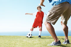 Small kid playing football with his father Stock Image