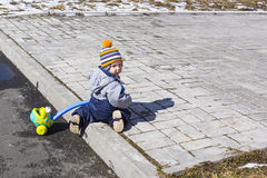 Small kid plays on the street Stock Photo