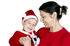 Small kid in Santa Claus clothes with his ​​grandmother Royalty Free Stock Images