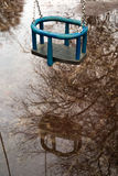 Small kid swing is not usable anymore. Childrens playground with little swing got flooded Royalty Free Stock Photo
