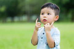 Small kid with two finger hold up. Asian young little boy at outdoor stock images