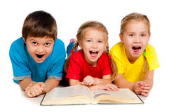 Small kids with a book. Small kids lie on the floor with a book against white Royalty Free Stock Photo