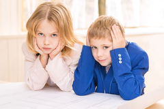 Small kids are leaning on table and frowning. Grumpy faces. Boy and girl are both mockingly frowning while leaning on the desk Royalty Free Stock Photos