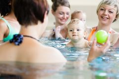 Babies and their moms at mother-and-child-swimming class stock images