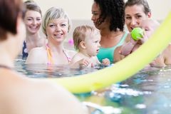 Small kids and their mothers playing with balls at baby swimming course stock images