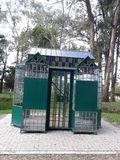 Small kiosk. A small kiosk with lots of glass, some decorated and colorful, green part, in a park stock image