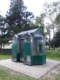 Small kiosk. A small kiosk with lots of glass, some decorated and colorful, green part, in a park stock photos