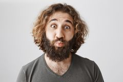 Small kiss for charming husband. Portrait of funny emotive eastern guy with curly hair and beard folding lips in mwah Royalty Free Stock Images