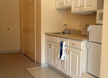 Small kitchen in apartment. Muted toned kitchenette in assisted living complex Royalty Free Stock Photography