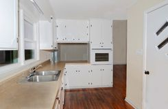 Small Kitchen Area in Home. A small kitchen that has been remodeled. White cabinets, wood flooring, bar pass thru area and an entry door stock images