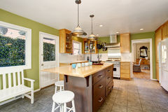Small Kitchen room interior with green walls and tile floor. Kitchen room interior with green wall and tile floor. Furnished with large wooden kitchen island Stock Image