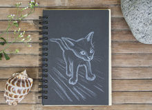 Small kitty exploring hand-drawn illustration. Cat by white chalk on black paper. Black paper notepad on wooden background. Vintage wooden table with artwork royalty free stock photos