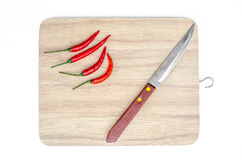 Small knife and red chilli on chopping board isolated white Royalty Free Stock Photo