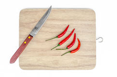 Small knife and red chilli on chopping board isolated on white Stock Photography