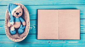Small knitted teddy bear and an open book with empty pages. A soft bear cub is in the basket. Copy space Royalty Free Stock Photos
