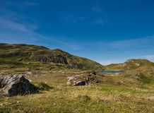 Small lake in a mountain landscape near Croaghlin. A small lake and green meadows in the mountain landscape of Croaghlin at Bunglass point stock images