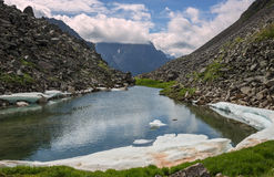 A small lake in the mountains Stock Images