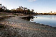 Small lake with sandy beach during sunset royalty free stock photo