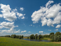 Small lake surrounded by trees and green meadows on a stormy aft Stock Images