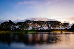 A small lake in summer at sunset. A small lake trees and clouds in summer at sunset Royalty Free Stock Images