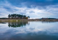 Small lake under dark cloudy sky. With sky reflected in water. Beautiful landscape Stock Photos