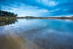 Small lake under dark cloudy sky. With sky reflected in water. Beautiful landscape Royalty Free Stock Images