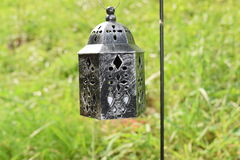 Small lantern on a pole. Small black lantern on a black pole surrounded by green grass Royalty Free Stock Photography
