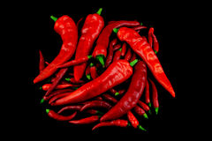 Small and Large Chilli Peppers on a Black Background Royalty Free Stock Photos