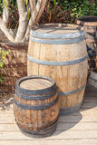 Small and large oak barrel planter decorations in garden. Royalty Free Stock Images